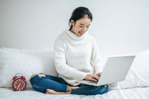 jovem vestindo uma camisa branca brincando em seu laptop foto
