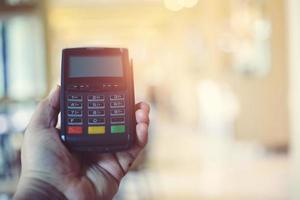 mão segurando máquina de cartão de crédito foto