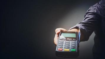 pessoa segurando máquina de cartão de crédito foto