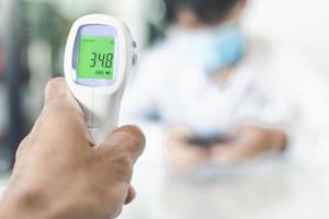 pessoa medindo a temperatura da pessoa desfocada
