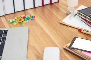 estação de trabalho bagunçada na mesa de madeira foto