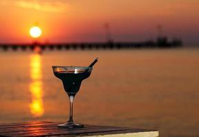 coquetel tropical com vista para o pôr do sol no oceano foto