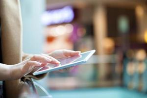 mulher com computador tablet em lugar público