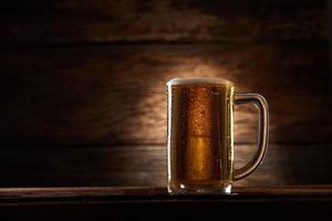 copo de cerveja na madeira foto