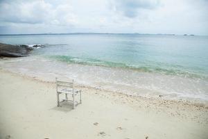 cadeira de madeira branca no mar foto
