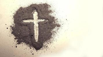 cruz feita de cinzas em fundo branco