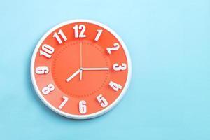relógio de parede laranja com fundo azul foto