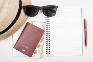passaportes, chapéu, câmera, óculos e caneta no chão de papel prontos para viajar