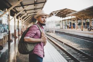 jovem hippie andando pela estação de trem foto