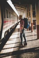 turista jovem hippie com mochila na estação de trem foto