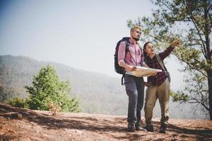 jovem casal de turistas caminhando para uma montanha foto