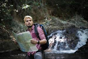 aventureiro observando mapa em um caminho de montanha