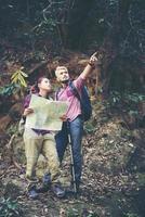 jovem casal de turistas viajando de férias na floresta foto