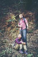 jovem casal de turistas caminhando na floresta foto