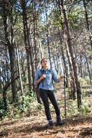 jovem com uma mochila relaxando ao ar livre em uma floresta de pinheiros