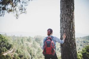 alpinista com mochila no topo de uma montanha foto