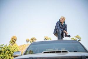 jovem fotógrafo sentado em sua caminhonete fotografando uma montanha