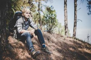 jovem viajando com uma mochila na natureza foto
