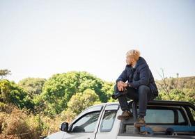jovem fotógrafo sentado em sua caminhonete
