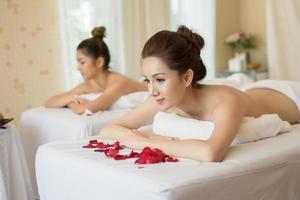 linda mulher sorridente com flores descansando no spa antes da massagem foto