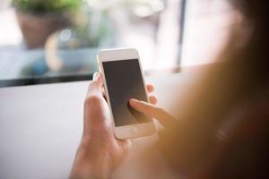 close-up das mãos de uma mulher segurando um telefone celular com a tela do espaço de cópia em branco foto