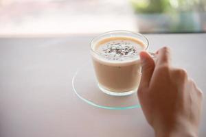 a mão de uma mulher com uma xícara de café em um café