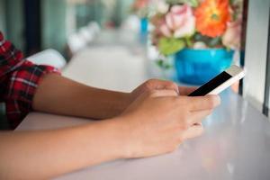 close-up de uma mulher segurando um telefone celular e digitando foto