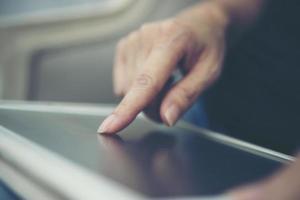 close-up das mãos usando o tablet sentado e relaxando foto