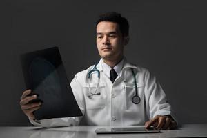 médico segurando o filme de raio-x de tórax do paciente no hospital.
