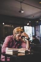 hipster barbudo homem lendo livro no café.