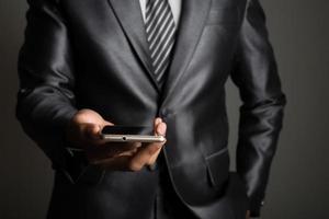 jovem empresário usando telefone celular isolado em fundo preto