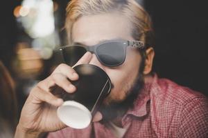 jovem sentado em um café e bebendo um café foto