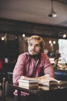 hipster barbudo homem lendo livro no café. foto