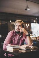 jovem hippie barbudo lendo um livro em um café foto