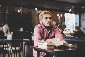 jovem hippie barbudo lendo um livro em um café