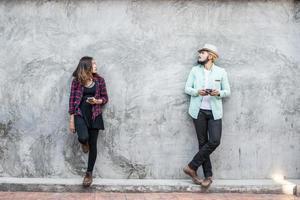 casal conversando com um celular na parede de tijolos, fundo vintage, grunge foto