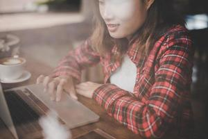 close-up de uma mulher trabalhando com seu laptop em um café