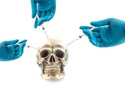 mãos usando luvas médicas injetando uma seringa no crânio foto