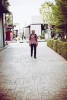 retrato de um homem bonito hippie em jeans e óculos de sol andando foto