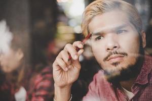 pensativo jovem hippie sentado em uma cafeteria pensando foto