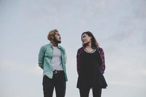 casal apaixonado de hipster em pé contra o céu claro foto