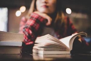 adolescente hipster sentado e lendo um livro em um café