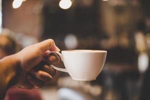mãos segurando uma xícara de café em um café com filtro vintage foto