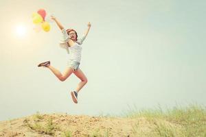 linda garota pulando com balões na praia