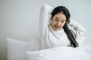 jovem sentada na cama com as duas mãos levantadas foto