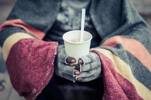 mendigo enrolado em panos comendo macarrão