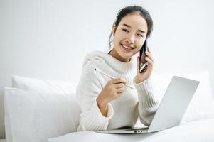 mulher brincando em seu laptop e falando ao telefone foto