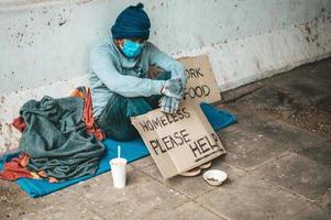 homem sentado ao lado da rua usando uma máscara médica com uma mensagem de morador de rua foto