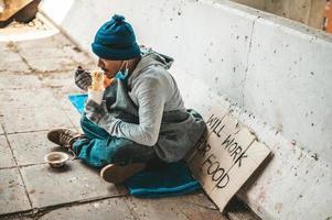 morador de rua enrolado em um pano comendo macarrão