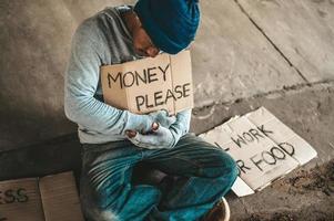 mendigo sentado debaixo de uma ponte com uma placa, dinheiro, por favor foto